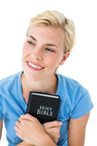 Pretty smiling blonde woman holding bible Stock Photography