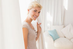 Pretty smiling blonde woman holding curtain Stock Photography