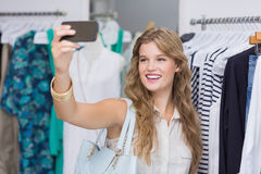 A pretty smiling blonde woman taking selfies Stock Image