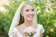 Pretty smiling bride holding her bouquet wearing a veil looking up Royalty Free Stock Photography