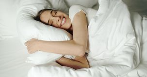 Hugging the Pillow. Pretty smiling brunette woman hugs pillow while lying in bed ,sunny morning close up shot stock video
