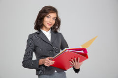 Pretty smiling business woman working with colorful folders. Pretty young curly happy smiling business woman in gray suit working with colorful folders stock photo