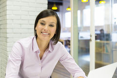 Pretty Smiling businesswoman working in office, lo stock image