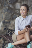 Pretty Smiling Caucasian Brunette Woman Relaxing on Bench and Listening to Music Royalty Free Stock Photo