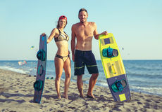 Woman kitesurfer enjoying summertime on sandy beach with her boyfriend. Pretty smiling Caucasian women kitesurfer enjoying summertime on sandy beach with her Royalty Free Stock Photo