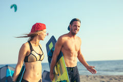 Woman kitesurfer enjoying summertime on sandy beach with her boyfriend. Pretty smiling Caucasian women kitesurfer enjoying summertime on sandy beach with her Stock Photography