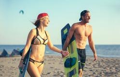 Woman kitesurfer enjoying summertime on sandy beach with her boyfriend. Pretty smiling Caucasian women kitesurfer enjoying summertime on sandy beach with her Stock Photo
