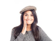 Pretty smiling and cheerful brunette woman with a french cap and a wool sweater royalty free stock photography