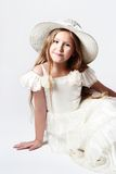 Pretty smiling child girl in white dress and hat Stock Image