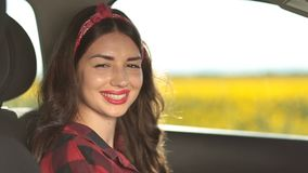 Pretty smiling female driver sitting in the car stock footage