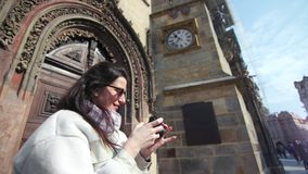 Pretty smiling female tourist taking photo of antique architecture using camera medium close-up. Happy travel fashion woman enjoying photographing vintage stock video footage