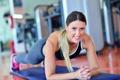 Pretty smiling fitness trainer doing push-ups in the gym. Young sportswoman exercising at aerobics class. Healthcare and weight lo Royalty Free Stock Photography