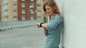 Pretty smiling fitness woman using running app before the run for track the pace on smartwatch, happy smiling sportive stock video footage