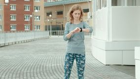 Pretty smiling fitness woman using running app before the run for track the pace on smartwatch, happy smiling sportive stock video