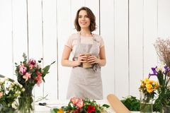 Pretty smiling florist woman with different flowers. Image of smiling florist woman standing near table with different flowers and looking aside in workshop Stock Photography