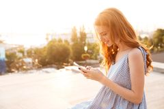 Pretty Smiling ginger woman in dress using smartphone Royalty Free Stock Photo
