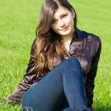 Pretty smiling girl. Sitting on the meadow Stock Images