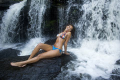 Pretty Smiling Girl in Bikini. Lovely happy young Hispanic African American woman smiles in front of a water fall stock images