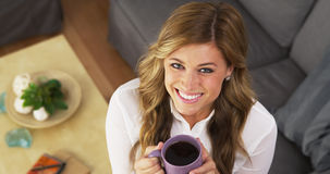 Pretty smiling girl drinking cup of coffee at home Stock Images