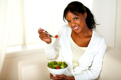 Pretty and smiling girl eating a salad Stock Image