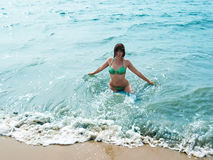 Pretty smiling girl in foaming waves of blue sea Royalty Free Stock Photos