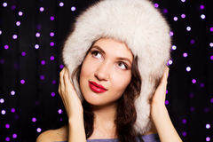 Pretty smiling girl in a furry winter hat. Beautiful woman is wearing white furry winter hat Stock Images
