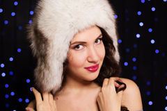 Pretty smiling girl in a furry winter hat. Pretty woman is wearing furry winter hat Royalty Free Stock Photography