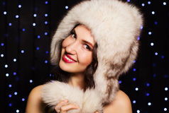Pretty smiling girl in a furry winter hat. Pretty smiling young girl in a furry winter hat Royalty Free Stock Image