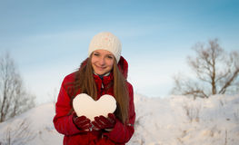 Pretty smiling girl holding a heart of snow. Love. Stock Photo