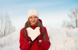 Pretty smiling girl holding a heart of snow. Love. Royalty Free Stock Images
