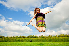 Pretty smiling girl is jumping on green meadow Royalty Free Stock Photo