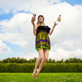 Pretty smiling girl is jumping on green meadow Royalty Free Stock Image