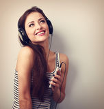 Pretty smiling girl listening the music wearing headphones holdi Royalty Free Stock Photography