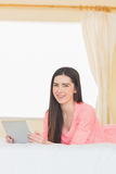Pretty smiling girl looking at camera and using a tablet pc layi Stock Photography