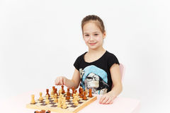 Pretty smiling girl play chess on white background Stock Photo