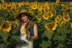 A pretty smiling girl. Relaxing and enjoying the moment among many sunflowers Stock Images