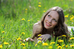 Pretty smiling girl relaxing outdoor in flowers Royalty Free Stock Photography