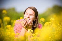 Pretty smiling girl relaxing on yellow flowers Royalty Free Stock Photo