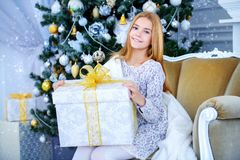 Opening gift box. Pretty smiling girl sitting in a armchair in a Christmas room and holding a gift. Merry Christmas and Happy New Year royalty free stock photo