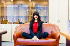 Pretty smiling girl sitting on sofa in the lotus position Royalty Free Stock Photos