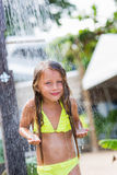 Pretty smiling girl standing under the spray of water in the shower on the beach royalty free stock photos