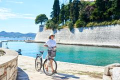 Young woman riding city bicycle near sea royalty free stock image