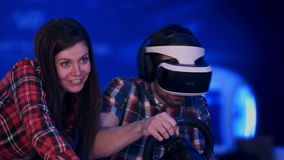 Pretty smiling girl watching her boyfriend playing racing video game in virtual reality headset. Professional shot in 4K resolution. 079. You can use it e.g stock video footage