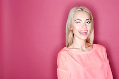 Pretty smiling girl winking on pink background Stock Images