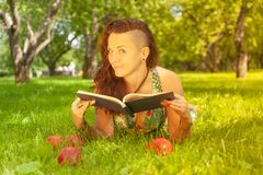 Pretty smiling happy girl in green dress reading book and lying on the grass stock photos