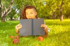 Pretty smiling happy girl in green dress reading book and lying on the grass royalty free stock image