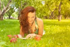 Pretty smiling happy girl in green dress reading book and lying on the grass royalty free stock photo