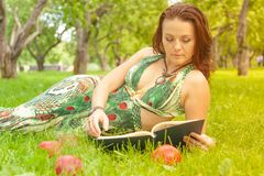 Pretty smiling happy girl in green dress reading book and lying on the grass stock images