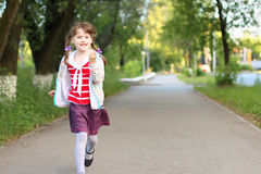Pretty smiling little girl with braids runs Royalty Free Stock Photo