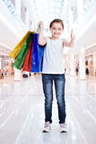 Pretty smiling little girl with shopping bags Stock Photo